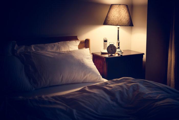 Mörkt sovrum där en lampa är tänd på nattduksbordet.