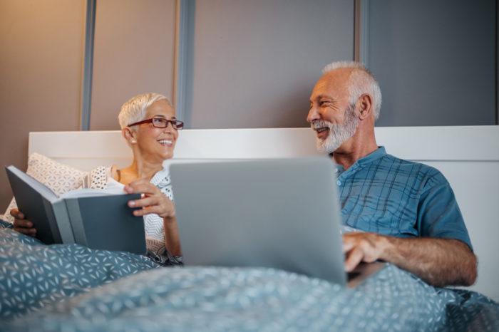 Äldre par ligger i sängen och läser.
