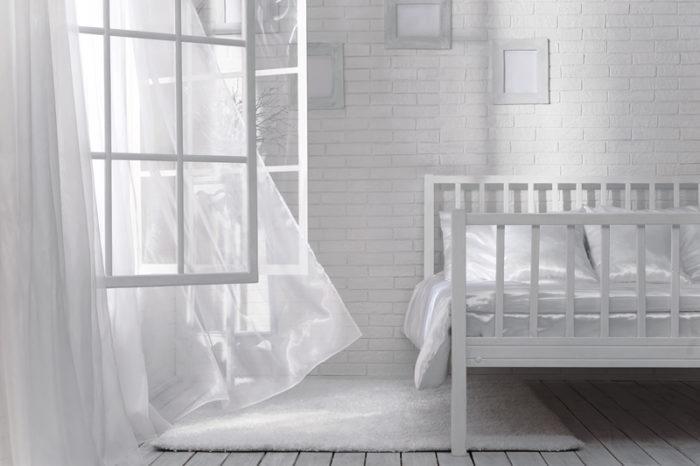 Sovrum helt i vitt där fönstret står öppet och gardinerna fladdrar i vinden.