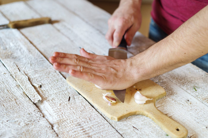 Man skalar vitlök med hjälp av bredsidan av knivbladet.