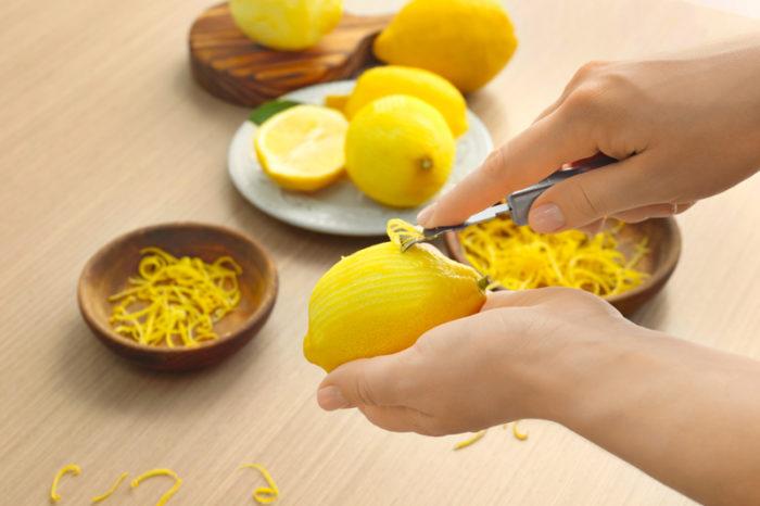 Tar zest från citron med hjälp av zestjärn.