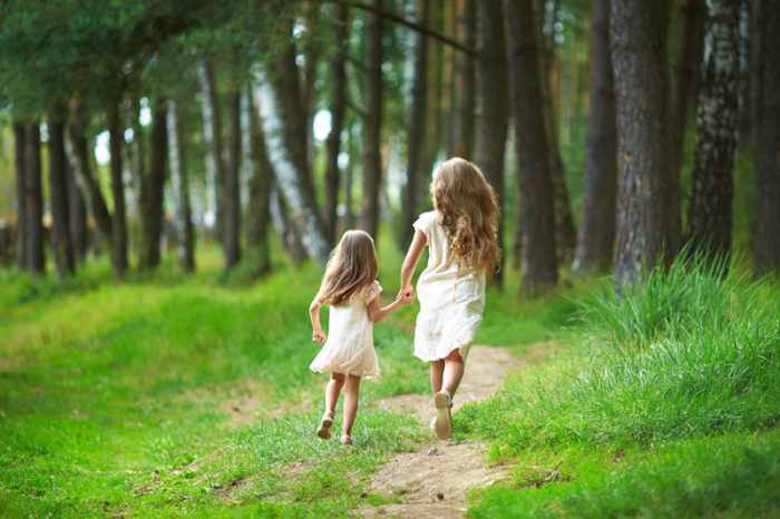 Två flickor i vita klänningar springer på en skogsstig.