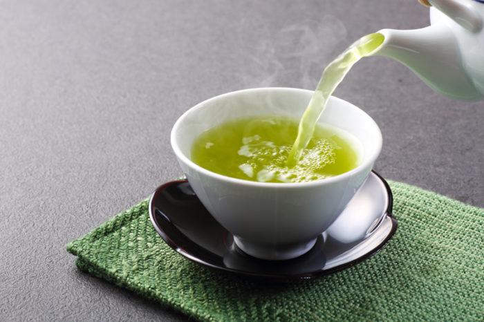 Grönt te hälls upp ur kanna ner i vit kopp.