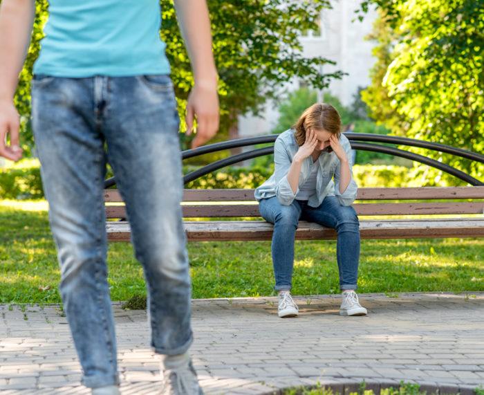 Ung kvinna sitter på bänk med nedslaget huvud efter ett bråk. I förgrunden är en ung man på väg ut ur bilden.