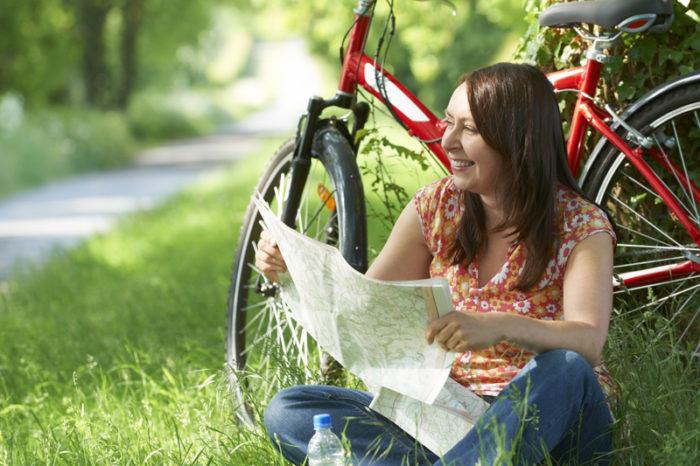 Kvinna sitter gräset bredvid en grusväg och läser en karta framför sin röda cykel.