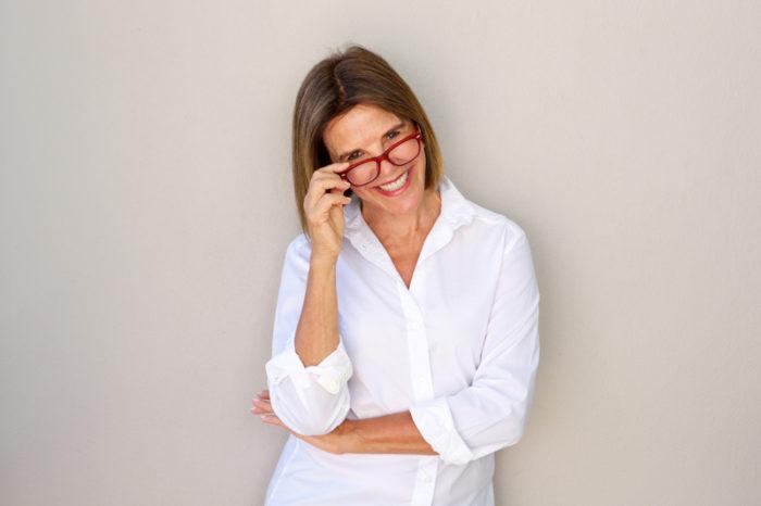 Kvinna i vit skjorta och röda glasögon.