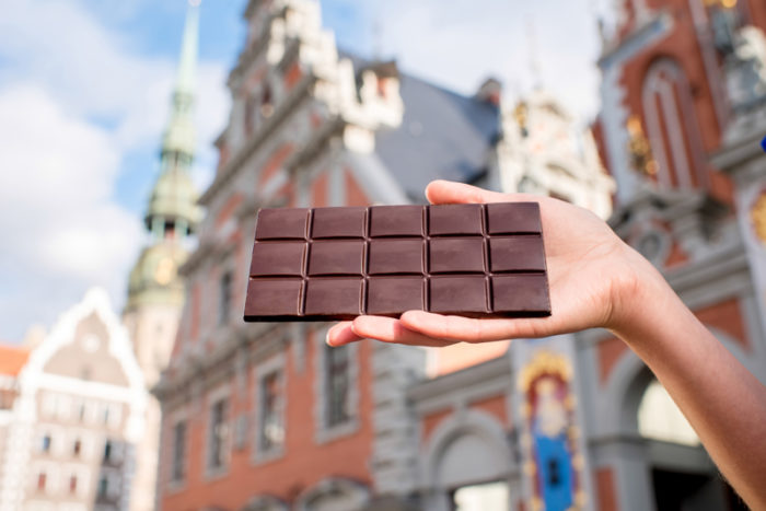 Kvinnohand håller i chokladkaka framför byggnader i gamla staden i Riga.
