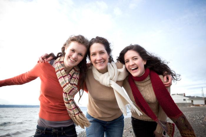 Två systrar och deras mamma på en strand.