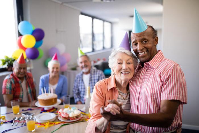 Ett äldre par med partyhattar står framför tre andra äldre personer som sitter vid ett bor i bakgrunden.