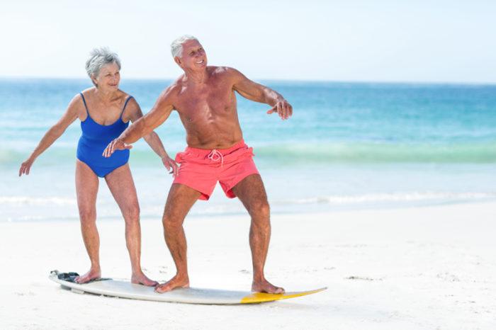 Ett äldre par, en man och en kvinna, står på en surfingbräda på en strand.