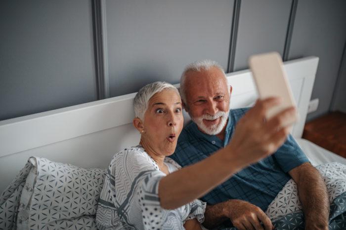 Äldre par tar en rolig selfie i sängen.