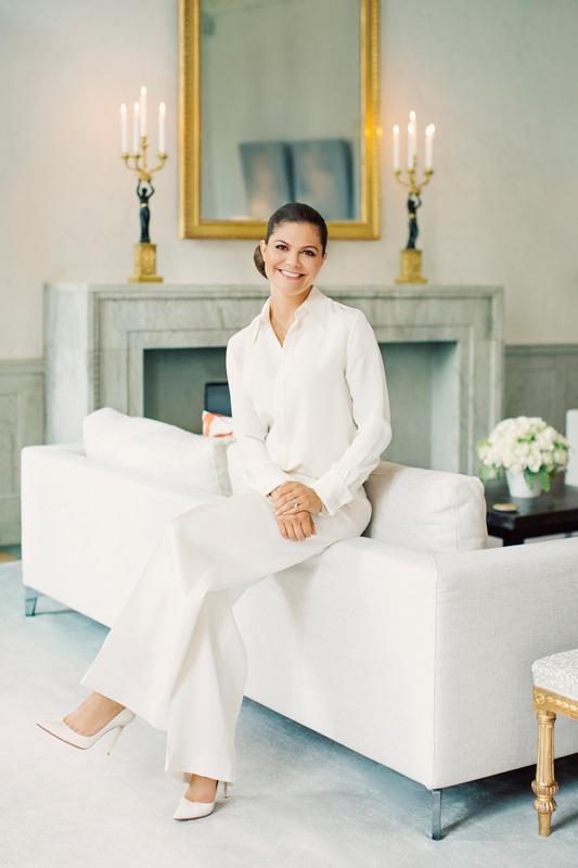 Kronprinsessan Victoria helt klädd i vitt sitter på ryggstödet till en vit soffa.