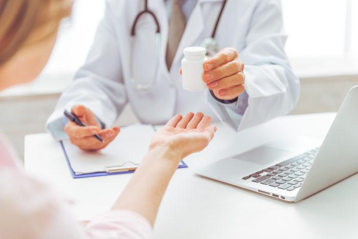 Läkare lämnar över burk med piller till kvinna.