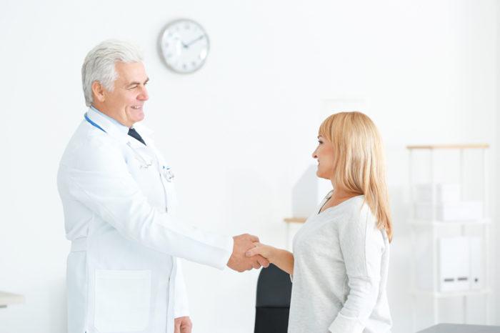 Manlig läkare och kvinnlig patient skakar hand.